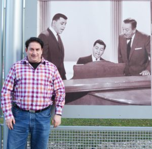 LAKE BUENA VISTA, Fla. (Dec. 20, 2016) – Robert J. Sherman, son of American songwriter and Disney legend Robert B. Sherman, poses by a picture of his late father [standing far left] on a wall of Disney music legends at the staging area for Disney Performing Arts participants.